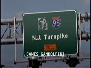 "The opening credit sequence to the show The Sopranos in which a car is driving through a tunnel and out into the sunlight, shot from the perspective of someone within the car. We then see a city skyline across a river. Shots of a sign for the New Jersey Turnpike, the twin towers, the car driving through a toll booth, the driver of the car smoking a cigar, lighting a cigar, semi-trucks on the other side of the road, construction zones, bridges, planes taking off, the Statue of Liberty, a train yard, industrial buidlings with smokestacks, the driver's face in the rearview mirror, a cathedral, a graveyard, storefronts, brownstone homes, and finally a nice suburban neighborhood flash by as the actors, producers, and other executives' names appear on the screen. The man pulls his car up in front of a fancy house and gets out of the car as The Sopranos logo appears on screen, the ""r"" in the shape of a pistol."