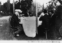 A black and white photo of six men in suits sitting around a clothed table outdoors.