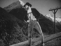 A man stands on a mountain slope. An electricity pole is behind him.