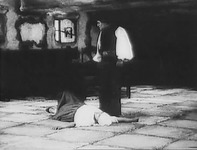 A man stands over a woman lying on the floor of a room.