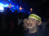 "A man in a concert crowd wears a headband reading ""God Bless the Pope"