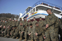 Two rows of a nearly a dozen men in camouflage fatigues, with the front row kneeling and the back row standing, bow their heads and cross their hands. Behind them is a colorful ferryboat.