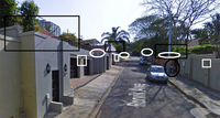 An image of a road in the Berea neighborhood of Durban, with security features like electric fences, cameras, contracted security companies, and an in-person guard, each feature framed in black or white boxes or circles.