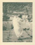 Photograph of Isadora Duncan dancing among ancient ruins in Athens. She wears a white chiton (a Greek-styled draping dress) and sandals, posing with arms outward and facing upward, mid-step with one leg bent.