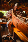 A color photograph of Erik Simula working on a birch-bark canoe.