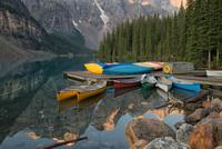 Canoes in a splash of colors await paddlers on Moraine Lake at Banff National Park in Alberta, Canada.