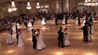Pairs of formally dressed people dance a waltz. Each couple spins as they step in time to the 1-2-3 pattern in the music.