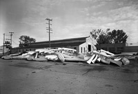 A large pile of Alumnacraft canoes in front of an old wooden warehouse.