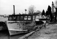 A photograph of the left side of a fisherman's boat sitting at the dock, from the front.