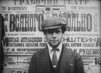 "In this film still, Eisenstein, in blazer, tie, and cap, looks out at the viewer of the film. The background behind him is filled with a large poster that introduces the term ""montage of attractions"" and advertises the May 8, 10, 12, and 13 performances of Wiseman."