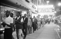 In 1963, a group of African American and white protesters march down a Raleigh sidewalk at night, clapping and singing freedom songs.