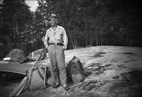 A black-and-white portrait of Olson standing on the shore next to a pack.