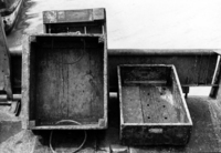 A photograph of three wooden crates, two propped up against a small barrier.