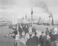A black and white photo shows people walking through the Galata Bridge.