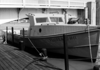 A photograph of the right side of a fisherman's boat, named Florence-H-11, sitting at the dock, from the front.