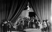 Photograph from the end of Princess Turandot. The actors hold the costume pieces they have just taken off while peeking out directly at the audience from the partially open curtain that the forestage servants pull back.