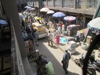 Kano market scene with men unloading wax-print textile bundles.