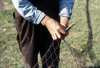 Close up of Don Hallock mending net.