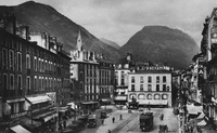 A postcard showing a photograph of the street view of Place Grenette, Grenoble. The angle of the photograph is aimed slightly upwards. Mountains are visible in the distance, beyond the buildings lining the street.