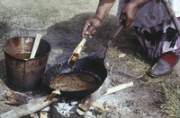 A color photograph of a figure cooking balsam fir pitch in an iron pan over an open flame.