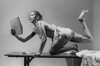 Carolee Schneemann kneels on a table with her right leg raised in the air while reading from Cezanne: She Was a Great Painter. She wears a white maid's apron and has paint lines along her body.