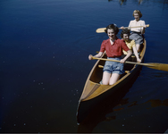 A color photograph of three young women with short haircuts in blouses and shorts sitting inside a wooden canoe on a lake.