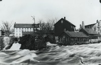 A photograph of the Grasse River sweeping by the Rushton Boat Shop, the white building at back left, during a flood in 1885.