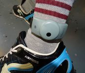 Photo of an electronic monitoring ankle bracelet on a peron's ankle, situated atop their sock.