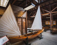 An all-wood decked sailing canoe with a double sail rig on display at the Antique Boat Museum in Clayton, New York.