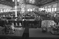 Fig05_01. A Kano textile mill with rows of tables with sewing machines, thread, and cloth.
