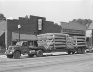 A black-and-white photograph of Grumman canoes loaded on a truck.