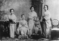 A black-and white-photograph of five girls, dressed in kimono. From the left, the first, second, and fifth girls are standing and the third and fourth are sitting.