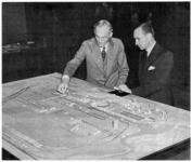 Henry and Edsel Ford examining a model of the River Rouge plant. The slip and turning basin can be seen, with the steel-making units to the left, and the storage bins, coke ovens, power house (tall stacks), blast furnaces, and foundry to the right.