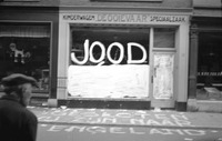 A vandalized shop with an antisemitic slur on its window and a message on the sidewalk indicating that the shop is closed.