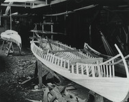Planking is applied to a pair of Indian Girl canoes in the Rushton Boat Shop, early 20th century.