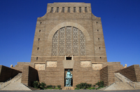 The Voortrekker monument in Pretoria is a large tan-colored building. Two stairways lead to the entrance from the right and left side of the building, along which are four carvings of a bull. The middle of the building is decorated with large archway of stone latticework. In front of the building is a statue of a woman with two children.