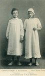 Photograph of Tyltyl (Khaliutina, left) and Mytyl (Koonen, right), holding hands, shoeless, dressed in stockings and three-quarter-length white nightgowns.