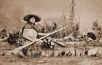 Black and white photograph of a woman posing with an oar in a dugout canoe. The canoe is full of vegetables, and the staged river is lined with vegetation.