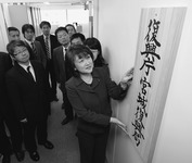 A woman hangs a vertical wood sign on the wall of an office hallway, while nine people in suits watch.