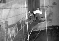Two strolling players, one a comedian (left), the other a tragedian (right), slowly descend an elevated catwalk that curves around the stage and ends in the orchestra pit.