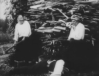 A woman holding an axe and a man stand in front of a pile of wood scraps. Between them, a man lies on the ground.