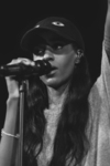 African American rapper Angel Haze in concert, at a microphone.