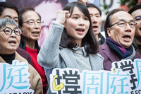 A young woman, Agnes Chow Ting, stands surrounded by a group of people chanting at a rally. Her right arm is raised, bent at the elbow, and she is making a fist. Several people hold signs with Chinese text