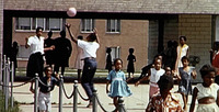 Color photograph of Black children playing ball of various ages and genders, with other children playing in front of them, facing the camera.