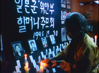 Film still from My Own Breathing  shows During a memorial service, a survivor lights a candle for former 'comfort women' who have passed away.