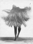 Photograph of Mary Wigman dancing solo in a straw costume, which obscures her body and makes her appear like a spirit with legs in tights. One leg is stepping up with the other lightly on the floor; only one arm is visible within the straw and is positioned away from her body.