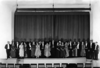 In this photograph, the cast of Princess Turandot stands on the forestage in evening dress, the curtain closed behind them, looking directly at the audience. Four commedia characters, their faces painted to look like masks, peer between them.