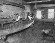 Sawdust litters the floor of the workshop at the Canadian Canoe Company factory as builders fashion canoes in distinctive shapes.