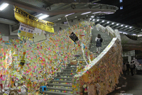 "A young woman climbs an outdoor staircase that is completely covered with Post-It notes bearing messages from activists. A banner hung from the ceiling reads, ""Lennon Wall Hong Kong"" while a sign over the staircase says, ""We are not alone"