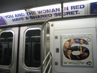 "A photo of an advertisement on a New York City subway train that says in capital purple letters ""You and the woman in red have a shared secret."" Beneath those words is the website ""u-r-connected.com."" Another ad on the subway features the tag line ""Everyone is Connected. From JJ Abrams, Producer of Lost""  with a graphic of 6 degrees beneath that includes images of 6 actors. Below are the words ""Six Degrees. Premieres Thursday September 21 10PM. ABC 7."""